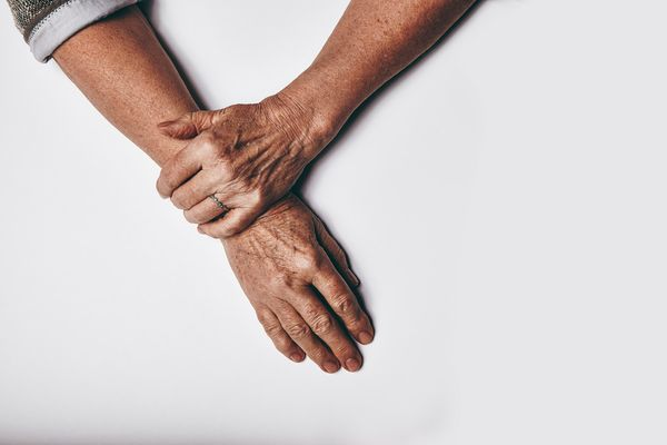 top-view-of-an-elderly-womans-hands-resting-on-grey-background-relaxed-old-female-hands-together_raGDZP8EYg_PMNW.jpg