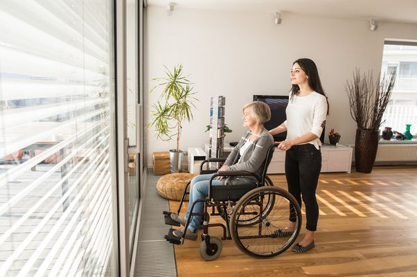 graphicstock-disabled-senior-woman-in-wheelchair-at-home-in-her-living-room-with-her-young-daughter-caring-for-her-looking-out-the-window_BuMnN_8MZ_PMNW.jpg
