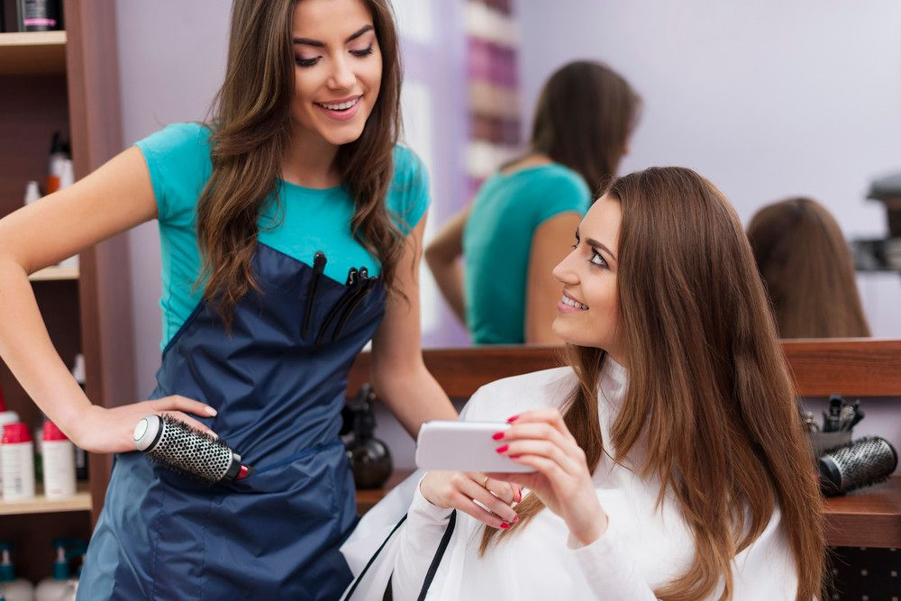 storyblocks-female-customer-showing-which-hairstyle-she-wants-on-mobile-phone_Hbw0lAwcM_PMNW.jpg