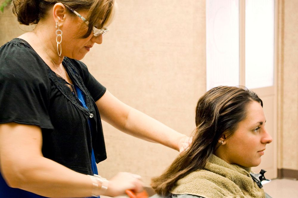 a-hairdresser-working-on-a-clients-hair-at-the-salon_BtVABuRBi_PMNW.jpg