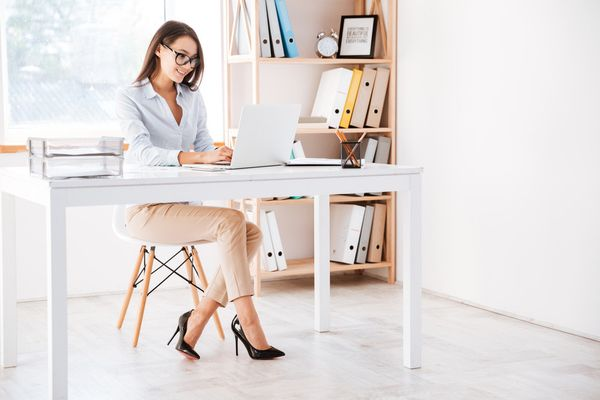 graphicstock-photo-of-businesswoman-dressed-in-white-shirt-and-wearing-glasses-sitting-in-her-office-and-using-laptop-looking-aside_S83xIYFXu2e_PMNW.jpg