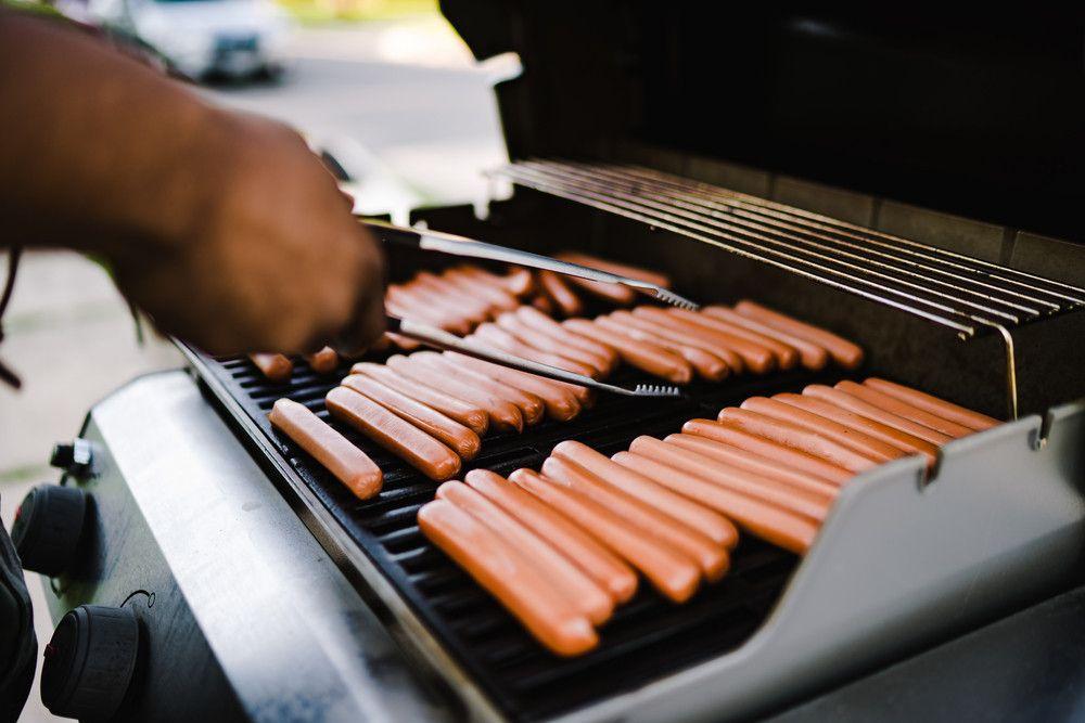 storyblocks-black-man-turning-over-hot-dogs-on-grill_ShLxN8D2Kw_PMNW.jpg